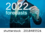 Small photo of economic forecasts for 2022. businessman writes forecasts for 2022 on a virtual screen. Post covid-19 economic recovery. Businessman in suit forecast analysis plan profit chart with pen