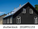 Black wooden house under a gray ...