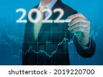 Small photo of Businessman in suit forecast analysis plan profit chart. economic forecasts for 2022. businessman writes 2022 on virtual screen. economic recovery after fall due to covid 19 coronavirus pandemic