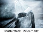 Gentle Car Washing. Modern Compact Car Covered by Water. Dark Blue Color Grading. - stock photo