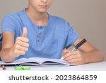 Boy hand holding pen in left...
