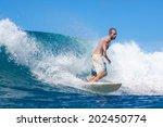 surfing a wave. lombok island.... | Shutterstock . vector #202450774