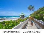 Women walking on boardwalk to beautiful Florida beach. Girls on summer vacation in Florida. Red Reef Park, Boca Raton, Florida USA.