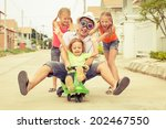 father and children playing near a house at the day time - stock photo
