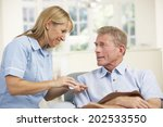 Small photo of Senior man visited at home by nurse