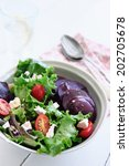 Bowl of salad with rocket, goat's cheese, beetroot, tomatoes and seeds  with glass of water and spoon - stock photo