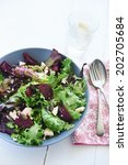 Bowl of salad with rocket, feta, beetroot and seeds  with glass of water, spoon and fork - stock photo