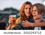 Small photo of A young tipsy couple is having a piggyback ride at a music festival. Man is singing while the girl holding a beer and having a good time.