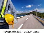 Engineer holding a yellow helmet for the safety of the workers. The background of the road on the dam catchment. Sunny afternoon