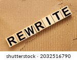 Small photo of concept word rewrite on cubes on a dark wooden background