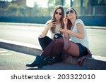 two beautiful young women using ... | Shutterstock . vector #203322010