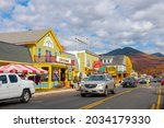 Small photo of NEW HAMPSHIRE, USA - OCT. 14, 2019: Lincoln Main Street at town center and Little Coolidge Mountain on Kancamagus Highway at the background with fall foliage, Town of Lincoln, New Hampshire NH, USA.