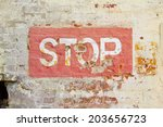 Red Stop Sign On Wall Of Bricks