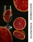 Small photo of A closeup shot of grapefruit slices and glasses of water on a specular surface against a black background
