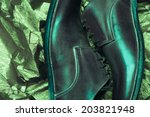 Stylish footwear fashion concept. Trendy brown leather men's shoes over olive-colored metal foil background. Close up. Vintage style. Studio shot - stock photo
