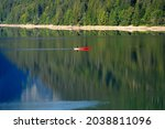 Fisherman In Red Canoe On A...