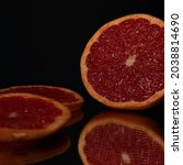 Small photo of A closeup shot of grapefruit slices on a specular surface against a black background