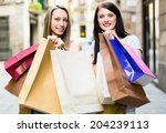 two girls with shopping bags on ... | Shutterstock . vector #204239113