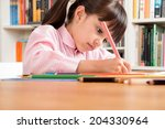 Small photo of Little school girl wearing an overall doing homework