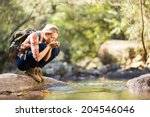 Young Hiker Drinking Stream...