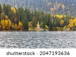 A beautiful autumn landscape with yellowed trees on the hills by a mountain Emerald Lake and a orthodox chapel on the shore. Natural seasonal background. Popular tourist destination, local landmark