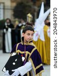 Small photo of Pontevedra, SPAIN - APRIL 17, 2014: A boy dressed acolyte wait to march in the procession of Holy Week.