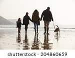 Rear View Of Family Walking...