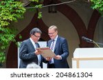 Small photo of BAMBERG, GERMANY - JULY 14 2014: 20 Year Anniversary Celebration of the Migration and Integration Advisory Board of Bamberg. Mayor Andreas Starke handing over a document to the Chairman