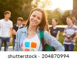 Small photo of Female smiling student outdoors in the evening with friends