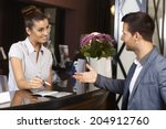 Stock photo happy receptionist and guest talking at hotel reception 204912760
