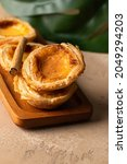 Small photo of Typical Portuguese sweet pastel de belem or pastel de nata on beige backgorund with green leave.