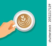 hand holds hot coffee cup....   Shutterstock .eps vector #2052217139