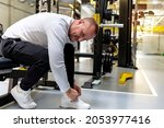 Small photo of Man tying his shoelaces in a gym. Athletic man tying shoelaces during rest after training in gym while sitting on the bench. Fit young man takes a short break from working out to tie his shoelace.