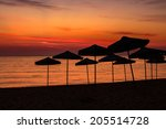 silhouettes of umbrellas on an empty beach at dawn sky background - stock photo