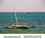 Small photo of Zanzibar, Tanzania - January 2021: Traditional dhow boat aground during low tide of the Indian Ocean. Africa