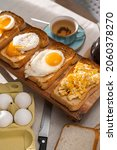 Small photo of fried Toast bread with four different types of cooked chicken eggs, scrambled eggs, fried eggs, poached egg and creamed egg. Breakfast of chicken eggs.