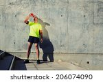 Stock photo young muscular build man with running armband on the arm drinking water of bottle attractive 206074090