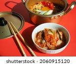 bowl of baechu kimchi on red...