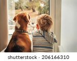 Stock photo little boy with best friend looking through window 206166310
