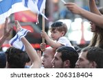 Small photo of NEW YORK CITY - JULY 20 2014: Several thousand attended a rally in Times Square to support Israel's recent actions in Gaza. Little boy with yarmulka & Israeli flags