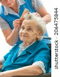 Caregiver Dressing The Hair Of...