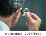 man inserts hearing aid in his... | Shutterstock . vector #206475910