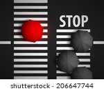 red umbrella and black umbrellas on a background of a pedestrian crossing