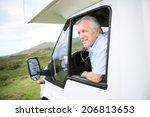 Senior man in motorhome sitting by steering wheel - stock photo