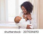 Happy Mother Feeding Her Baby...