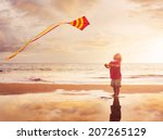happy young boy flying kite on... | Shutterstock . vector #207265129