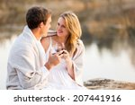 cute young couple sitting by a... | Shutterstock . vector #207441916