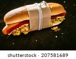 Small photo of Delicious hot dog with a smoked Vienna sausage and salad ingredients with tomato sauce and mustard tied in a brown wrapper against a dark background