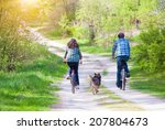 Stock photo young happy couple ride bicycles in the village back to camera dog running nearby 207804673