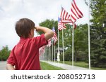A Young Boy Salutes The Flags...